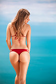 A beautiful woman, back view, over sea background at summer