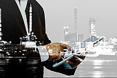 Double exposure of success businessman using digital tablet with landscape of oil refinery background