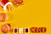 Top view hamburger, french fries and fried chicken on yellow background. Copy space for your text