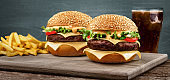 Two craft beef burgers on wooden table on blue background