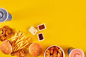 Fast food dish top view. Meat burger, potato chips and wedges. Take away composition. French fries, hamburger, mayonnaise and ketchup sauces on yellow background