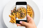 Shooting food on phone's camera. Meat with mushroom sauce and french fries