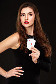 Sexy curly hair brunette posing with two aces cards in her hands, poker concept isolation on white background