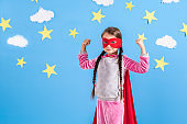 Six year blonde girl dressed like superhero having fun at home. Kid on the background of bright blue wall