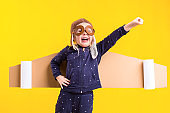 Freedom, girl playing to be airplane pilot, funny little girl with aviator cap and glasses, carries wings made of brown cardboard as an airplane