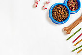 Dry pet food in bowl and bone on white background top view