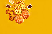 Fast food and unhealthy eating concept - close up of fast food snacks on yellow background