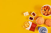 Fast food dish top view. French fries, hamburger, mayonnaise and ketchup sauces on yellow background