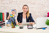 Mom and businesswoman working with laptop computer at home and playing with her baby girl