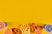 Fast food dish on yellow background. Fast food set fried chicken, meat burger and french fries. Take away fast food