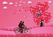 Concept of valentine day ,with a heart shaped tree and lovers ride bicycle paper art and craft style