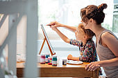 Millennial mom painting on a canvas with her daughter