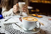 Cup of hot coffee with beautiful woman drinking latte behind