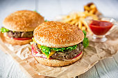 American hamburger with beef, sauce and french fries on wood background. Flat lay. Top view.