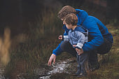 Young dad with young son by stream