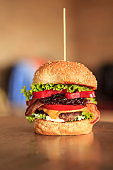 Freshly flame grilled burgers in a row on wooden board
