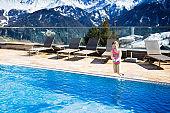 Child in outdoor swimming pool of alpine resort