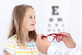 Child at eye sight test. Kid at optitian. Eyewear for kids.