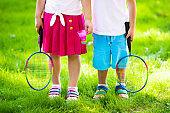 Kids play badminton or tennis in outdoor court