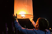 Asian man holding floating sky lanterns during Loy Kratong Festival