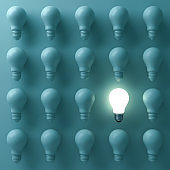 One glowing light bulb standing out from the unlit incandescent bulbs on green background with reflection , individuality and different creative business bright idea concepts . 3D render