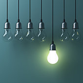 One hanging light bulb glowing different and standing out from unlit incandescent bulbs with reflection on green background , leadership and different business creative idea concept. 3D render