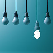 One hanging energy saving light bulb glowing different stand out from unlit incandescent bulbs with reflection on dark cyan background , leadership and different creative idea concept. 3D render