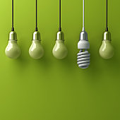 One hanging eco energy saving light bulb different and stand out from old incandescent lightbulbs with reflection on green background, individuality and different creative idea concept