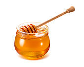 Honey jar with wooden dipper isolated on white