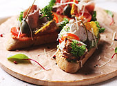 Bruschetta sandwich with ham, herbs and tomatoes on round board
