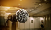 Microphone on abstract blurred of front podium and speech in seminar room or speaking conference hall light, Event meeting bokeh background, black and white tone