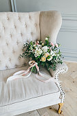 Rustic wedding bouquet with creamy roses and white carnations on a luxury cream sofa. Close-up. Side view