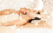 couple in spa salon getting face treatment