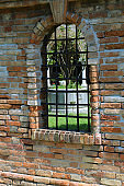 Window with metal grating and brick wall