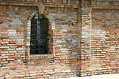 medieval Window with metallic grating in the middle of the brick