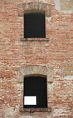 two Windows of an old brick building with iron grilles