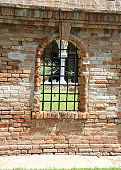 medieval Window with metal grating in the middle of the brick wa