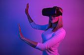 Women testing Virtual Reality simulator at multi colored room