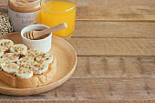 Banana peanut butter toast sandwich on wood plate with honey. Homemade open sandwich spread with peanut butter on top with banana slice and granola. Delicious healthy sandwich for breakfast or lunch.