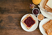 Toast bread with homemade strawberry jam and peanut butter served with orange juice. Homemade toast bread with jam and peanut butter on table for breakfast. Delicious toast bread in top view flat lay.