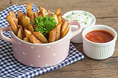 Homemade french fries serve with ketchup and sour cream or mayonnaise. Golden brown crispy french fries sprinkle with salt and oregano in pink bowl for snack or appetizer. French fries on wood table.