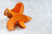 Pumpkin slices on a wooden background