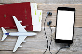 Plane tickets, passports, smartphone with earphones, and toy plane
