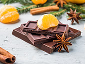 Fresh tangerines with branches of Christmas tree, star anise chocolate cinnamon on gray concrete background