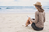 Young woman reading book on a beach