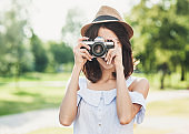 Young woman taking photographs with photo camera