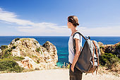 Young woman traveler looking at the sea
