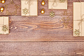 frame made of homemade wrapped christmas and new year present boxes and decoration on wooden background with copy space for text. holiday and celebration concept. above view, flat lay.
