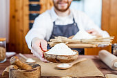 Man holding wheat flour in a bakery close up