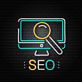 Vector isolated neon sign of computer and magnifier glass for decoration on the wall background. Concept of Search Engine Optimization.